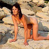 Female nudist on a rocky beach.